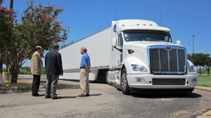 Peterbilt representatives Don Vollmar, Director of Product Planning (left) and Rick Mihelic, Manager of Vehicle Performance and Engineering Analysis (right), present the advanced concept SuperTruck vehicle for U.S. Rep. Michael C. Burgess, M.D., (center) during the Energy Summit & Fair in Denton, Texas.